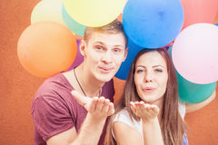 Young people sending a blow kiss to the camera. Couple celebrate birthday or some International holiday like World Kissing Day or Valentine's Day Royalty Free Stock Images