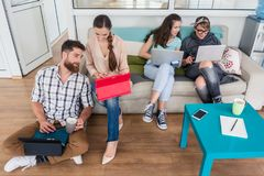 Young people sharing a collaborative office space in a modern hu. Happy young people laughing while sharing a collaborative office space as co-workers in a royalty free stock photo