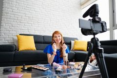 Young People Shooting Makeup Video For Vlog Video Blog. Happy girl at home talking about makeup in front of camera. People and technology, young woman at work as Stock Photography