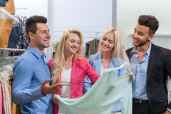 Young People Shopping, Happy Smiling Friends Two Couple Customers In Fashion Shop. Choosing Clothes Stock Photography