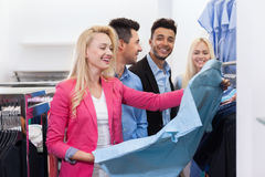 Young People Shopping, Happy Smiling Friends Two Couple Customers In Fashion Shop. Choosing Clothes Shirts Stock Photos