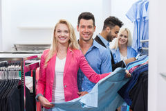 Young People Shopping, Happy Smiling Friends Two Couple Customers In Fashion Shop. Choosing Clothes Shirts Royalty Free Stock Photo