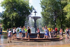 Young people showered each other with water from a fountain. Stock Photography
