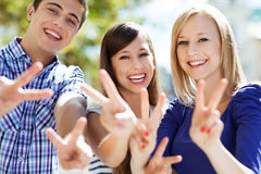 Young people showing peace sign. Portrait of young people smiling Stock Photography