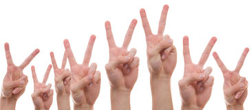 Young people showing the peace sign. Teenagers raising their hands with two finger symbolizing peace Stock Image