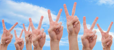 Young people showing the peace sign. Teenagers raising their hands with two finger symbolizing peace Royalty Free Stock Photography