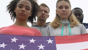 Young people silently holding American flag honoring shooting victims, mourn. Stock footage stock footage