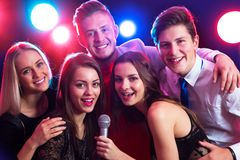 Young people singing at party. Young people singing into microphone at party Stock Image