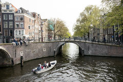 Young people sit on bridge over amsterdam canal while small boat Stock Photography