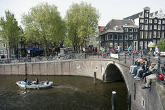 Young people sit on bridge over amsterdam canal while small boat Royalty Free Stock Image