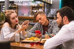 Young people sitting in the bar and looking at the screens of devices stock image