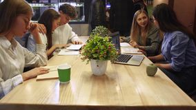 Young people sitting in a cafe at the table reading magazines and books. Students spend time in fast food healthy eating. Preparing for exams stock video footage
