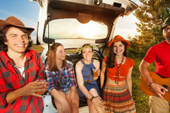 Young people sitting in car boot enjoying the trip Royalty Free Stock Photos