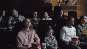 Young people sitting at the cinema, watching a film and eating popcorn, friendship and entertainment concept. 4K stock footage