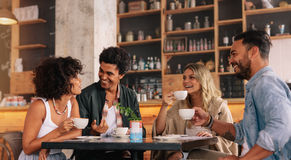 Young people sitting at a coffee shop. And talking. Group of friends having coffee together in a cafe stock image