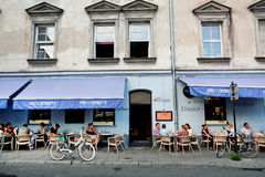 Young people sitting outdoor around the tables of restaurant in old city Stock Photo