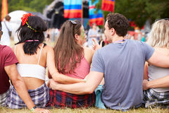 Young people sitting outdoors at a music festival, back view Stock Image
