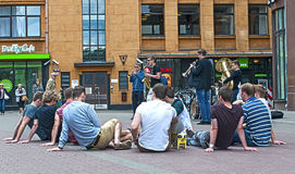 Young people sitting on the pavement in Riga Royalty Free Stock Photos