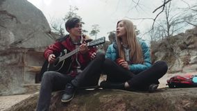 Young people sitting on the rock and singing a song, young man playing the guitar, and charming blonde girl drinking hot. Tea, smiling. Enjoying each other stock video footage