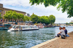 Young people sitting by the Seine river at the tip of Ile de la Stock Photos