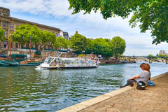 Young people sitting by the Seine river at the tip of Ile de la Stock Photo