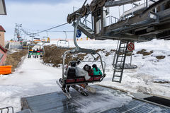 Young people sitting on ski lift with seats and going to the slo. Pes in a ski-resort in winter period Royalty Free Stock Image