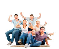 Young people sitting on a sofa cheering Stock Photo