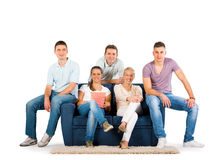 Young people sitting on a sofa smiling Royalty Free Stock Images