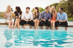 Young people sitting by swimming pool stock photography
