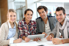 Young people sitting at the table and using tablet Stock Image