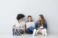 Young people sitting and talking with a computer stock images