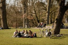 Young people sitting in Vondelpark in Amsterdam Netherlands. March 2015. Landscape format royalty free stock photos
