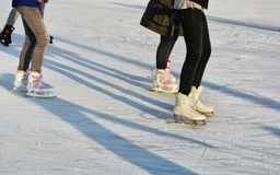 Young people skate on ice skating rink Stock Images