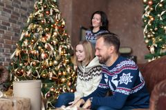 Young people smiling while sitting near Christmas tree with Christmas gifts Stock Photos