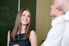 Young people solve a problem on a board Stock Photo
