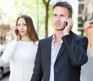 Young people speaking on phones separately. Young people walking around city and speaking on phones separately Royalty Free Stock Images