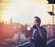 Young people spend time on the terrace of the house, blowing bubbles with the help of vaporizer against backdrop of the sunset Royalty Free Stock Image
