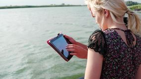 Young people spending time watching films on ipad, boy and girl using tablet at lakeside stock footage