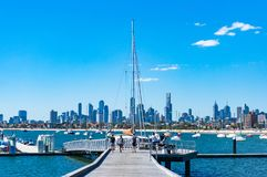 Young people on St. Kilda pier with Melbourne cityscape on the b. Melbourne, Australia - December 7, 2016: Young people on St. Kilda pier with yachts and Royalty Free Stock Photography