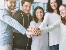 Young people stacking hands. College students and friends stacking hands together and smiling, teamwork and collaboration concept royalty free stock photos
