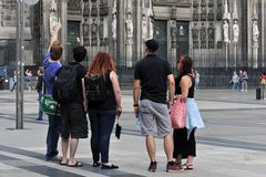The young people stand in front of the Cologne Cathedral. Royalty Free Stock Images