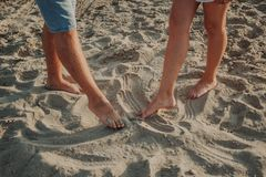 Two pairs of legs draw on the sand figures royalty free stock photo