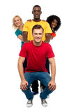 Young people standing behind semi seated guy Stock Photo