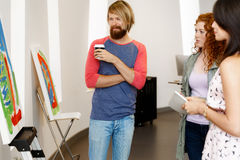Young people standing in a gallery and contemplating artwork Stock Photography