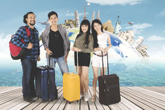 Young people standing on seaside with landmark. Multi ethnic of young people standing on seaside while holding suitcase with famous landmark background stock photography