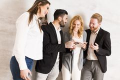 Young people standing by the wall and hold phones in hands. Young people standing by the wall and hold cell phones in hands stock photography