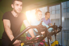 Young people on stationary bike Royalty Free Stock Photos
