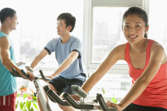 Young people on stationary bikes exercising in the gym Royalty Free Stock Photos