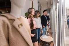 Young people stay near mannequin at store window. Three people pretend to be dummy at clothes shop showcase. Young two women men stay near mannequin at store stock photography