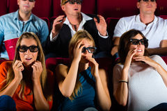 Group of people watching 3d movie at movie theater. Young people strained watching 3d movie at movie theater Stock Images